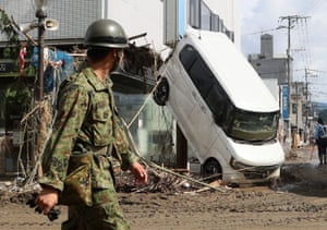 An officer walks past a damaged car in Hitoyoshi, in Kumamoto prefecture