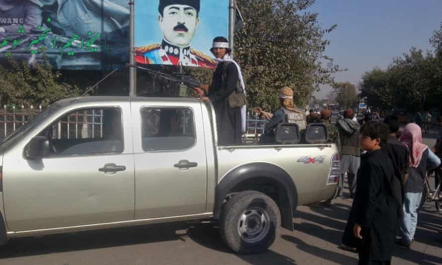 A Taliban fighter stands guard on a vehicle in Kunduz.