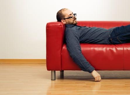 Pria tidur siang di sofa