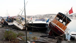 Damaged boats on a beach after the sea surge in Bodrum
