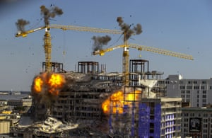 Louisiana, USExplosives experts detonated charges to topple two cranes standing precariously over the partially collapsed Hard Rock Hotel in New Orleans.