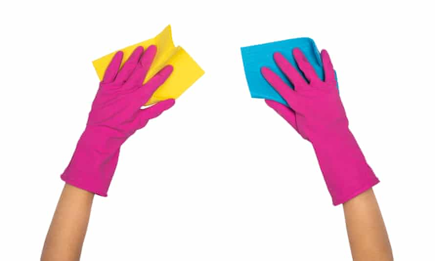 A pair of hands in pink rubber gloves holding cloths