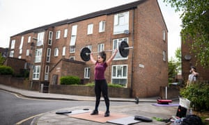 a woman works out with weights on a street corner