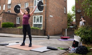 Crossfitter Elena Demou (L) is watched by personal fitness trainer James Luong as she lifts weights by the side of the road on a housing estate in London.