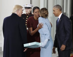 Michelle Obama, greets Melania Trump at the White House, who arrives with a gift