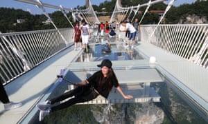 A tourist takes a selfie on the glass-bottom bridge.