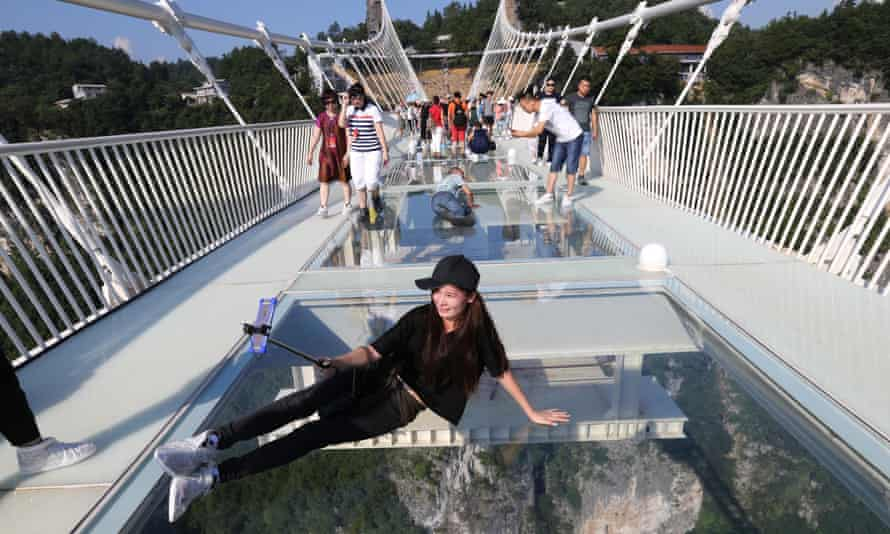 A tourist takes a selfie on the glass-bottom bridge.