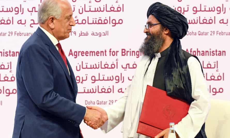 US Special Representative Zalmay Khalilzad and Taliban co-founder Mullah Abdul Ghani Baradar shake hands in Doha, Qatar.