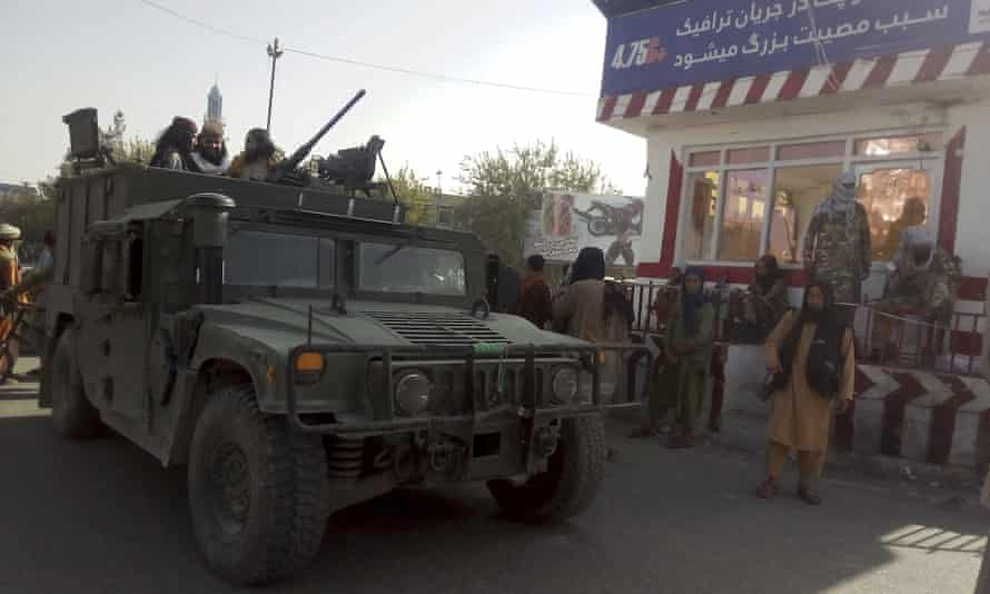 Taliban fighters stand guard at a checkpoint in Kunduz, northern Afghanistan