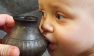 A reconstruction of a baby being fed using a vessel