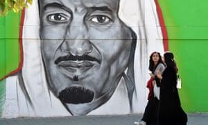 Women walk past a mural of King Salman in the Saudi capital, Riyadh