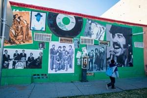 A boy walks past a mural of Steve Crosno