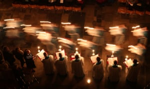 Choristers on a candle-lit advent procession through Salisbury Cathedral in Salisbury, England