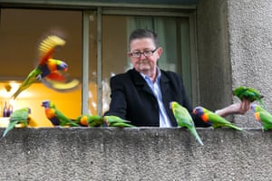 Lee feeds the lorikeets from his balcony in the Banks building