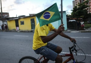 A cyclist carries the Brazilian flag along the Olympic torch route.