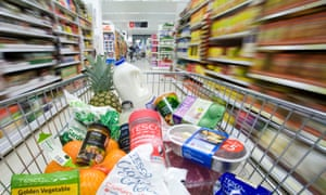 A shopping cart filled with items is pushed down the aisle at a Tesco supermarket in London