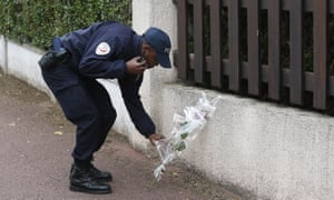A French police officer lays flowers while paying tribute to his colleagues killed in a knife attack near their home in Magnanville.