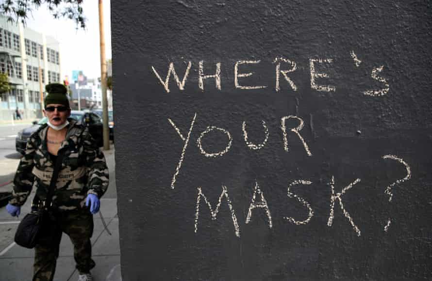 A San Francisco pedestrian passes graffiti encouraging masks during the coronavirus outbreak.