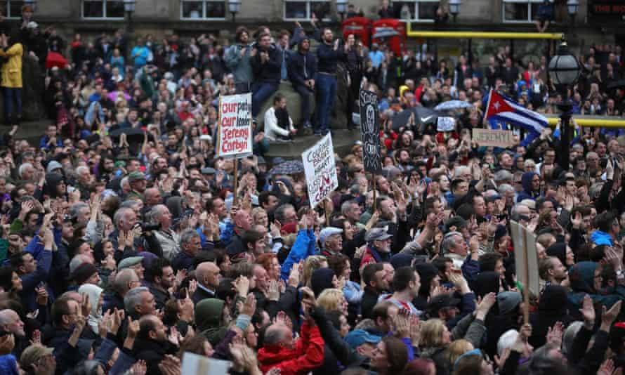 People cheer and wave placards as Labour Leader Jeremy Corbyn addresses thousands of supporters in St George's Square, Liverpool.