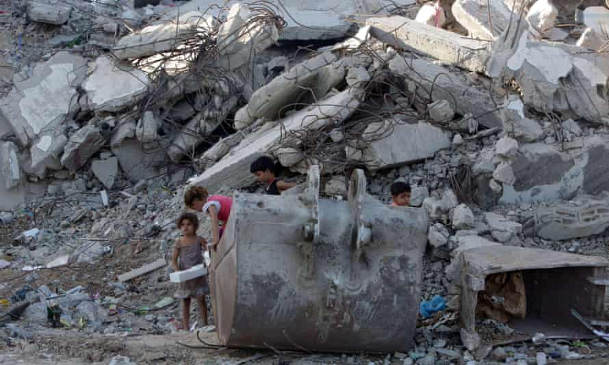 Palestinian children play in the rubble of buildings in Gaza City that were destroyed by Israel in the summer of 2014.