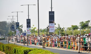 People wait beside a street to catch a glimpse of US president Donald Trump's motorcade in Ahmedabad
