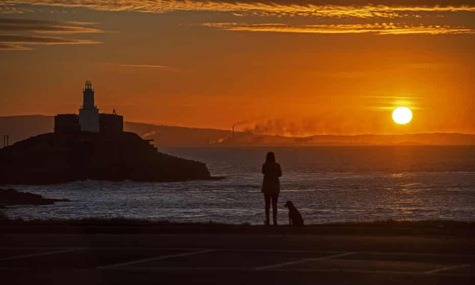 A woman walking her dog pauses to take in the autumn sunrise alongside the Mumbles Lighthouse on the Gower Peninsula near Swansea.