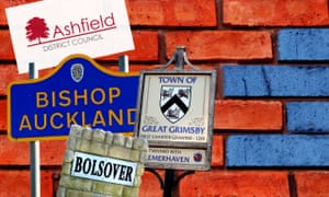 Town signs of Ashfield, Bishop Auckland, Great Grimsby and Bolsover in front of a red brick wall with some blue bricks encroaching.