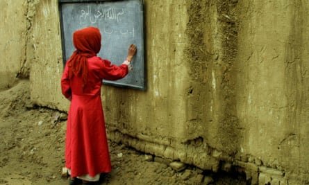 In March 2002 in Kabul, an Afghan girl learns the Dari alphabet during a lesson in an ourdoor classroom. Girls who the Taliban banned from education were attending classes for the first time in six years.