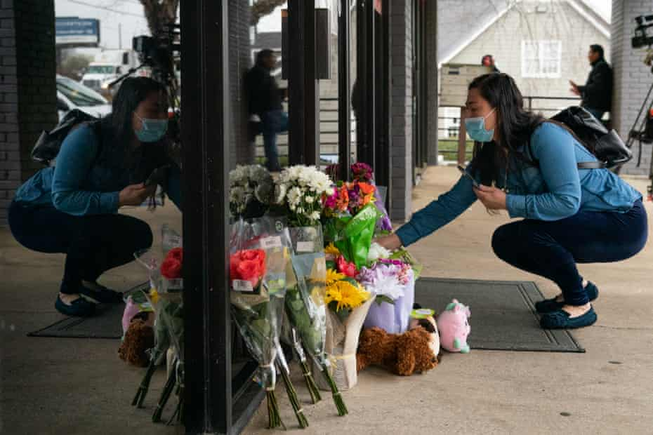 Lijing Zhao, owner of Jo Jos Massage, places a bouquet of flowers outside the spa where four people were shot and killed in Acworth, Georgia, on 17 March.