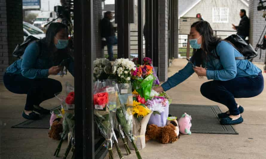 A mourner lays flowers at the scene of one of the shootings in Atlanta. 'Anti-Asian hate crimes have been rising in the US since 2015'.