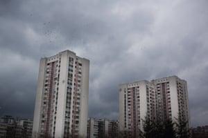 Dark clouds above. A flock of birds fly overhead. Sarajevo, March 2015