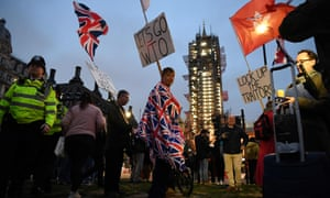 Brexit supporters carry flags and placards as they walk gather in Parliament Square