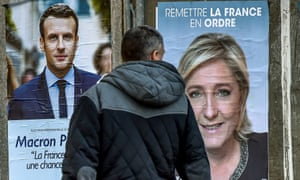 A man looking at campaign posters of French presidential election candidates