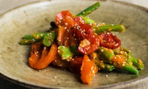 A rustic plate of broad and green beans with preserved tomatoes.