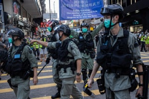 Police clear a street during a silent march against the national security law in Hong Kong