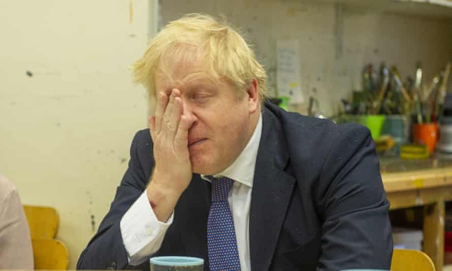Boris Johnson holds his hand to his face