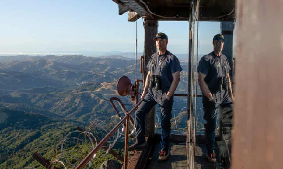 Rory Hewitt stands on the edge of a tower on Mt Tamalpais, California, where he is a volunteer lookout for wildfire ignitions.