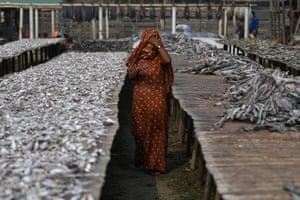 A Rohingya refugee woman walks through Nazirartek fish-drying yard where she works