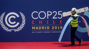 A worker walks past a COP25 logo at the IFEMA Convention Centre in Madrid.