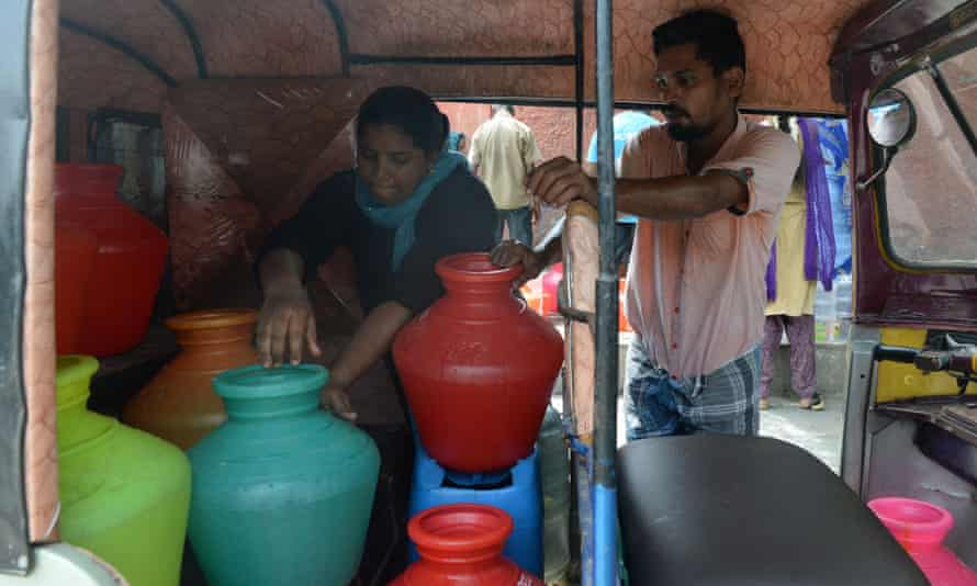 Residents arrange plastic pots filled with drinking water in an auto rickshaw at a distribution point in Chennai