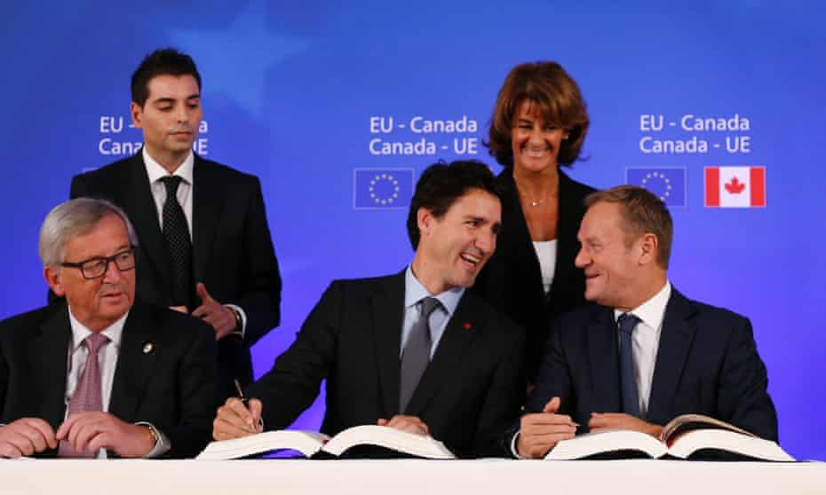 Jean-Claude Juncker looks on as Justin Trudeau shares a joke with Donald Tusk