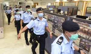 Police officers inside Apple Daily headquarters
