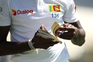 Kasun Rajitha of Sri Lanka signs a copy of The Alchemist by Brazilian author Paulo Coelho for a member of the crowd during day three of the Second Test match between Australia and Sri Lanka at Manuka Oval.