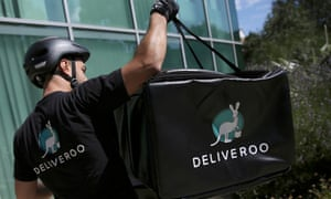 A Deliveroo worker loads his bicycle after making a delivery in London