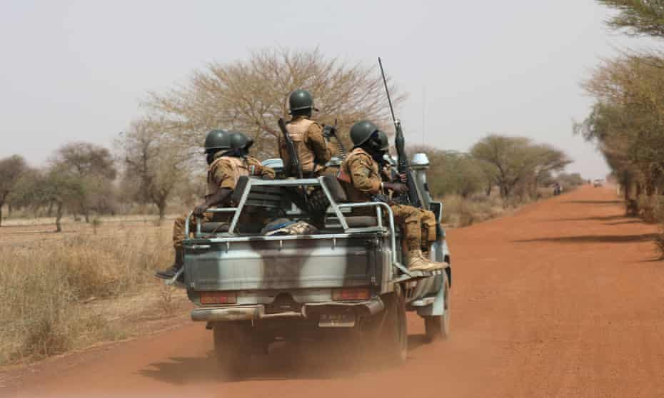 Burkinabe soldiers patrol the road near the town of Gorgadji, in the Sahel area of Burkina Faso.