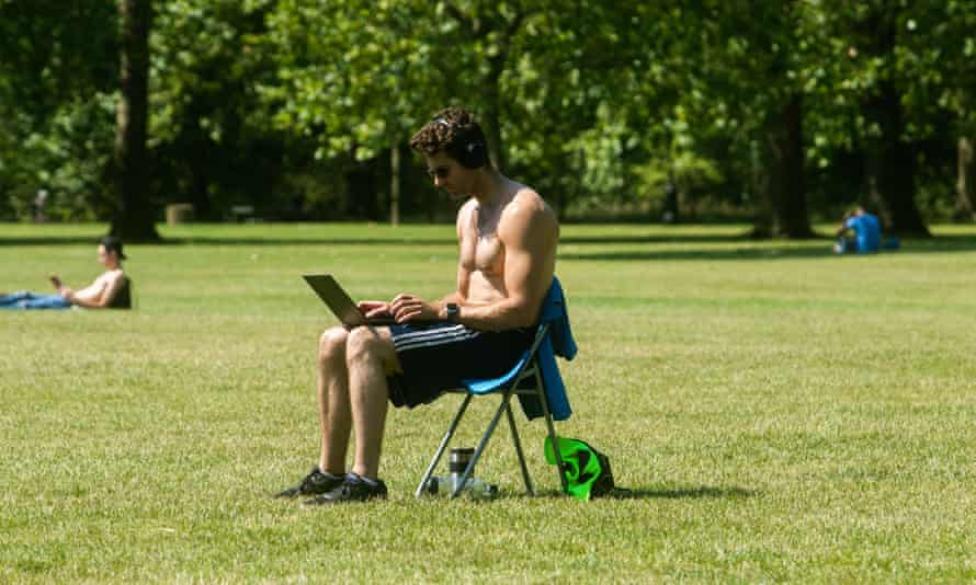 A man working on a laptop in Green Park, London, June 2020.