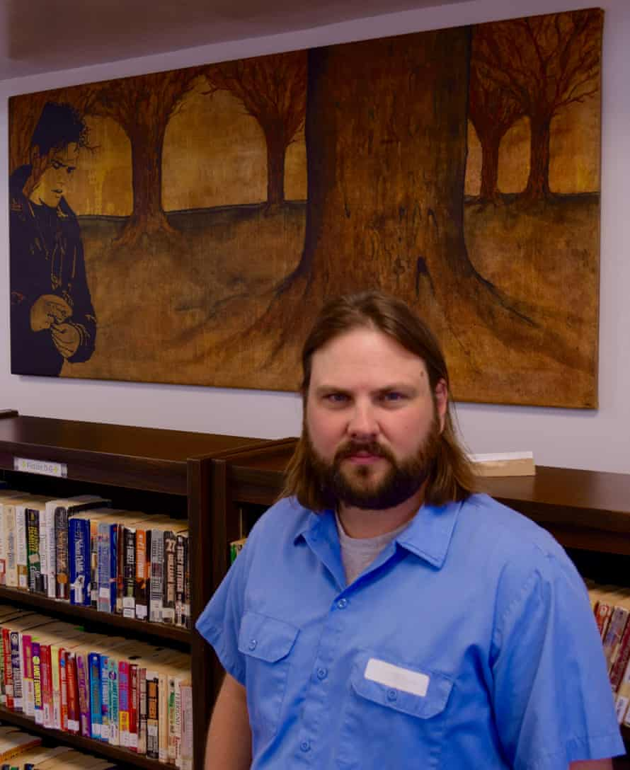 Livingston in the library with one of his paintings in the background.