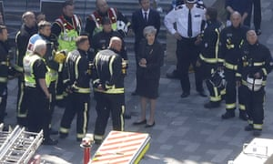 Theresa May at Grenfield Tower talking with members of the emergency services.