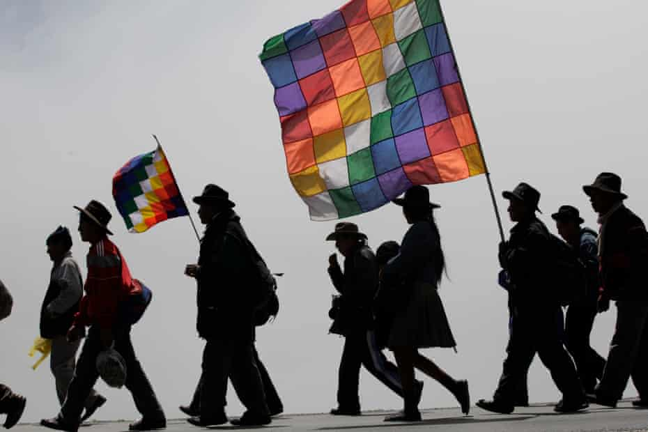 Protesters carry flags representing their indigenous movement in Bolivia.