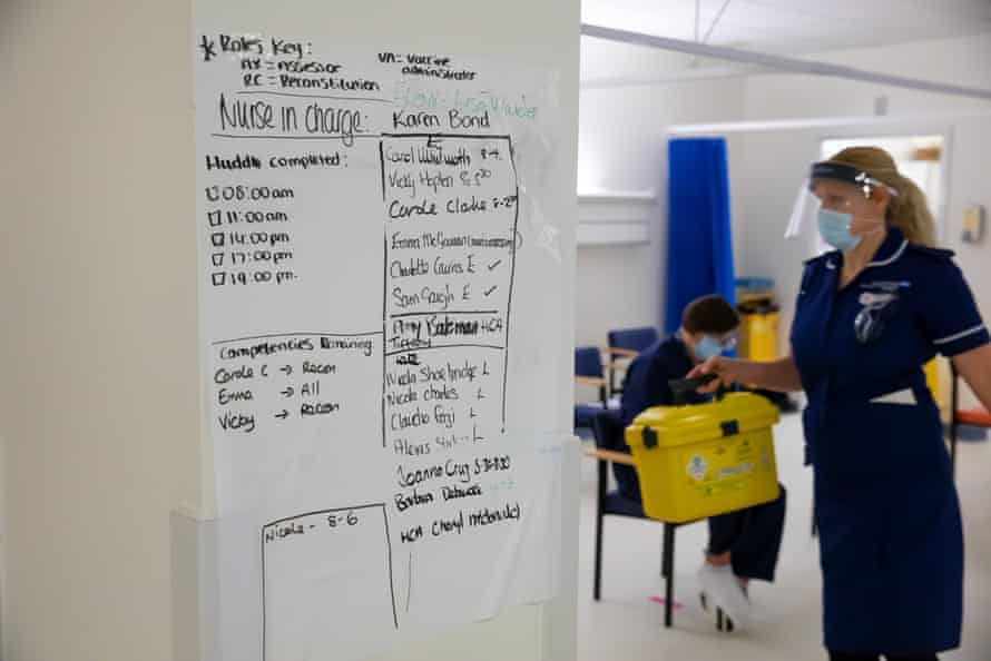 The staffing schedule inside the vaccine rollout room as a nurse carries away a box of used needles.